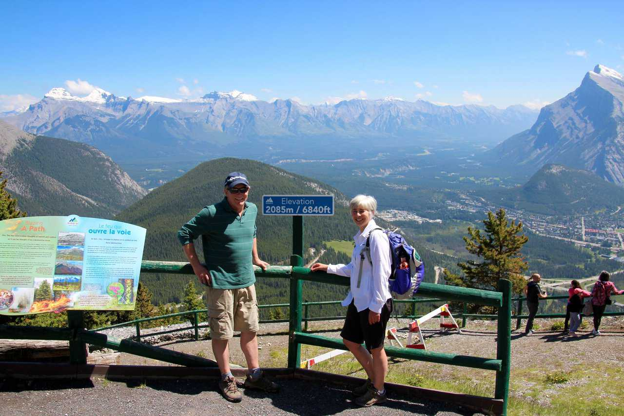 picture of two people at the Elevation sign on Mt. Norquay.