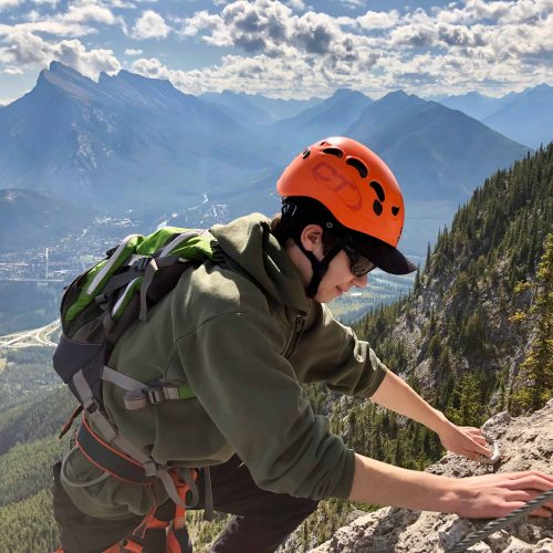teen climbing on a via ferrata route mt. norquay