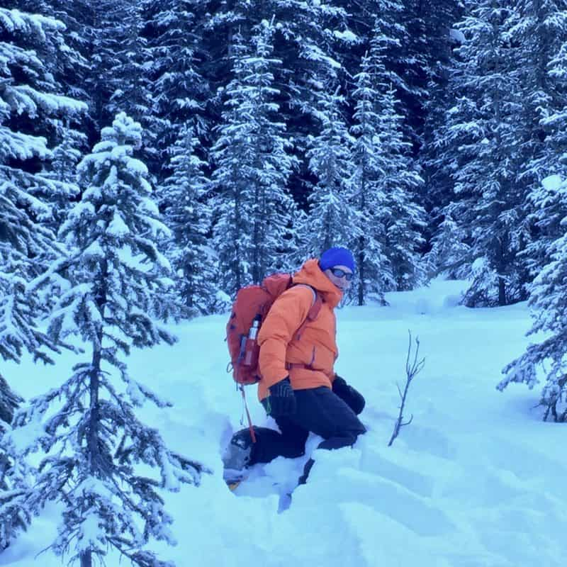 man snowshoeing in deep snow at Hogarth Lake in Alberta