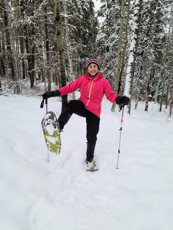 a women balancing on one leg with snowshoes on