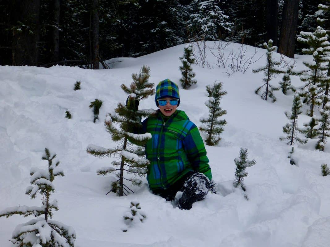 young boy playing in deep snow
